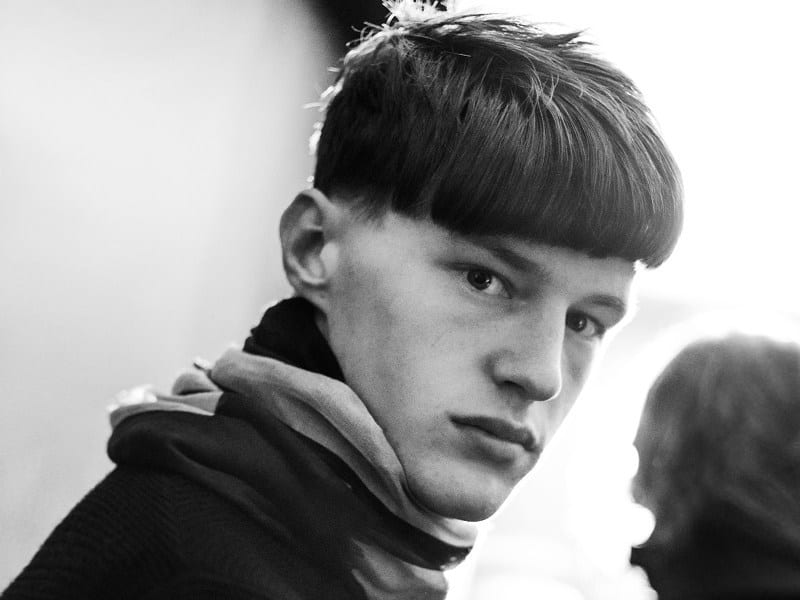 An astonished guy with a bowl-cut hairstyle