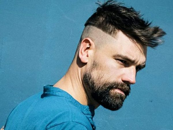 A fellow with a beard and undercut hairstyle