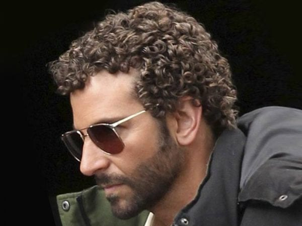 A man with sunglasses and Jerry curl hairstyle