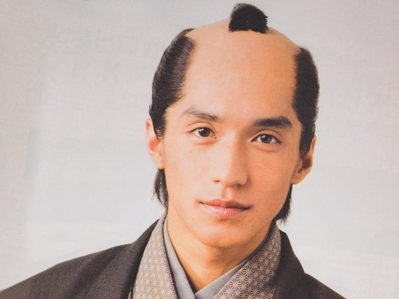 An Asian man with a chonmage hairstyle for men.