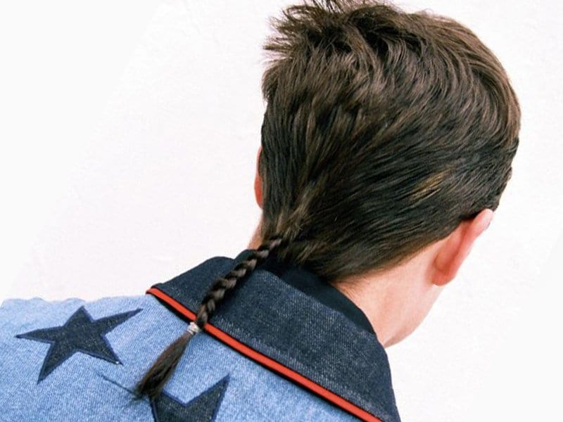 The back view of the guy with a rat-tail hairstyle for men.