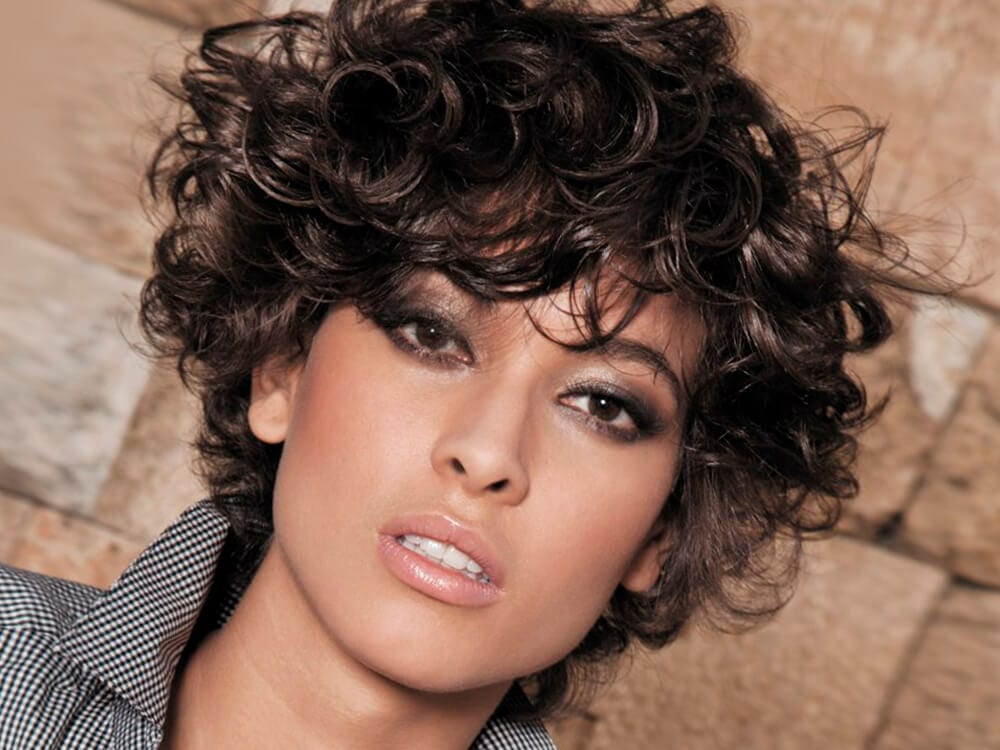 A female with short curly hairstyle.