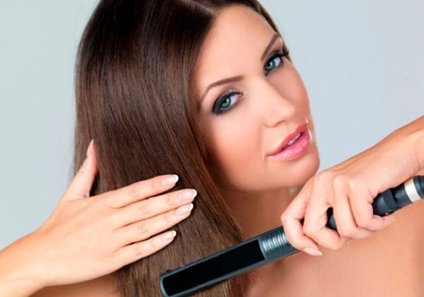 a female who is straightening her hair