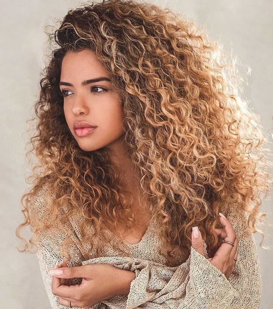 Black girl with long dirty blonde curly hairstyle