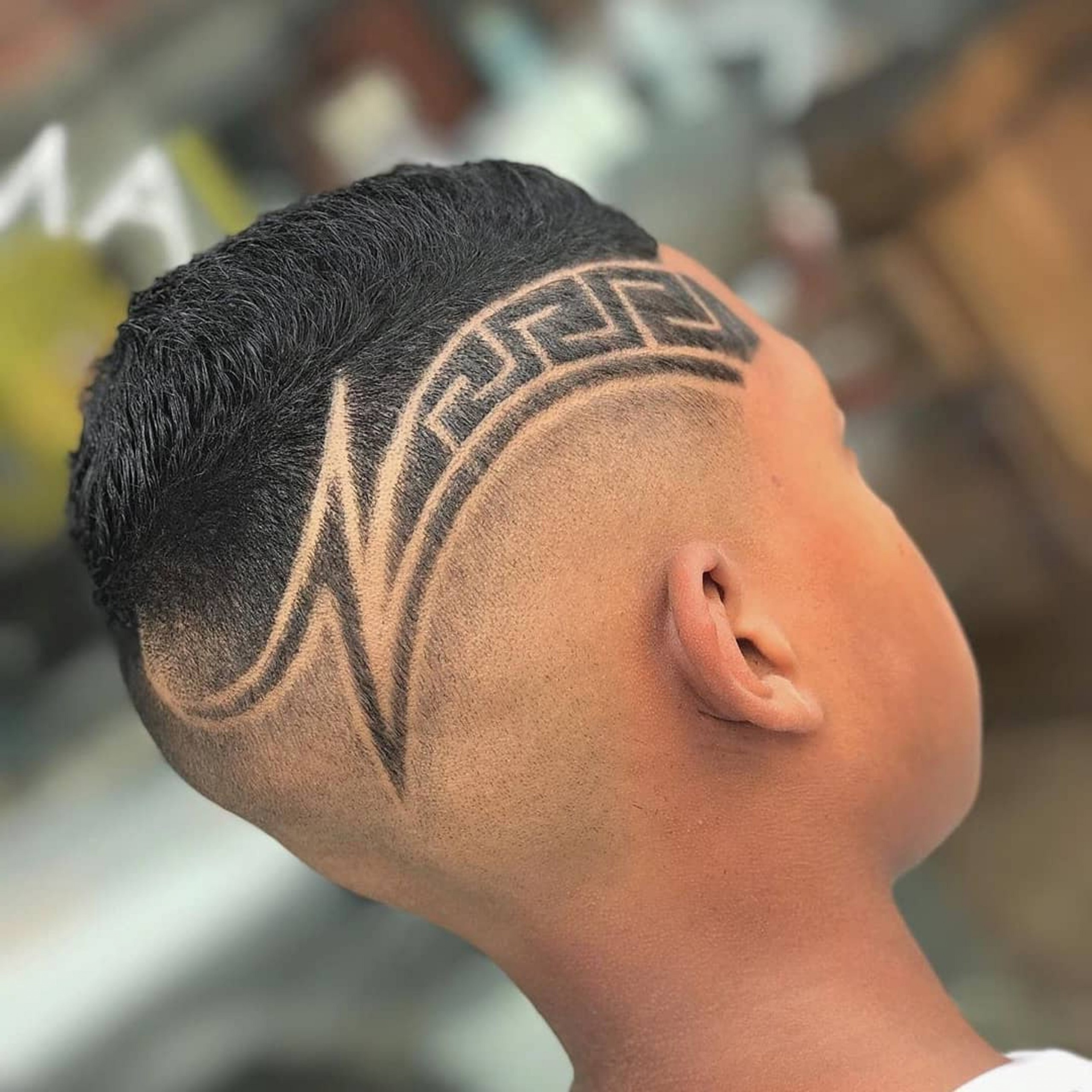 A faded haircut with an original design for boys.