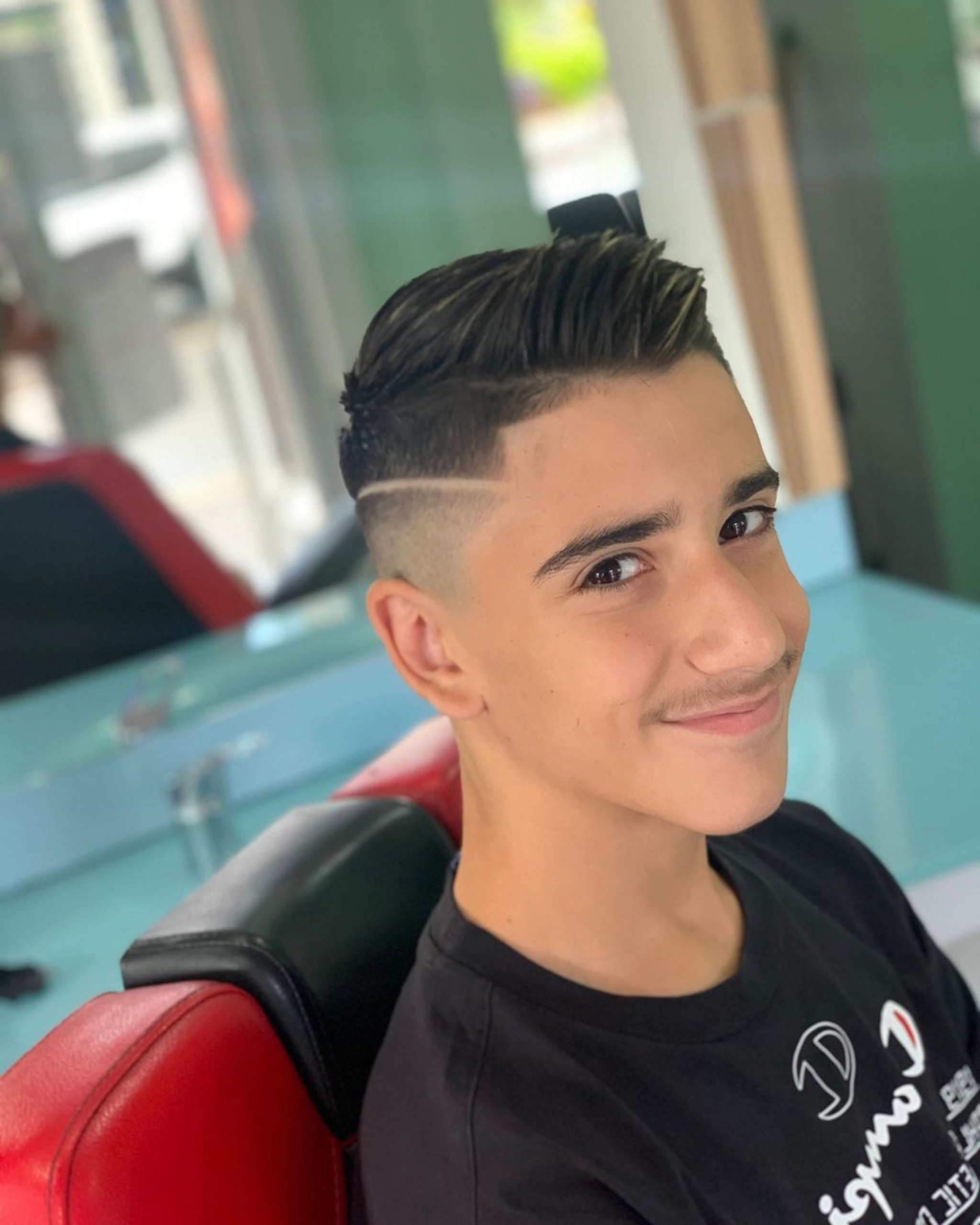 A faded side-part haircut for boys.