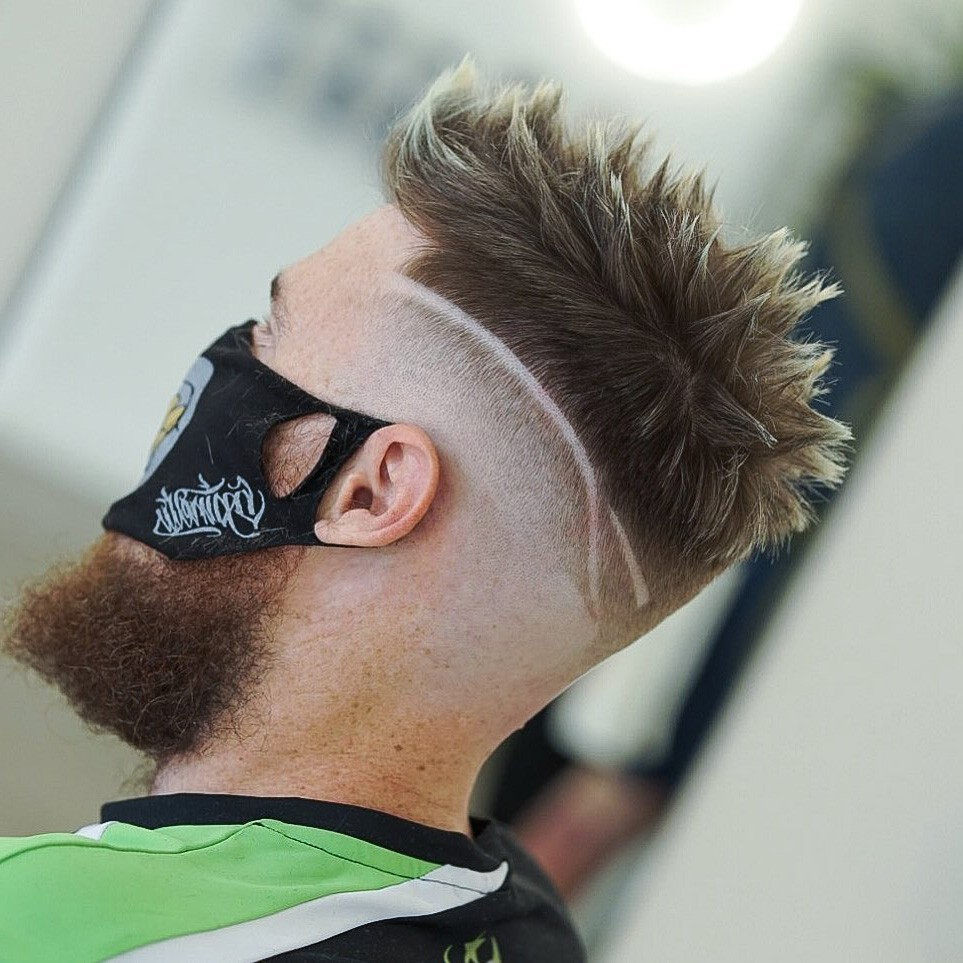 A man with a full beard and a temp fade haircut with spiky hair.