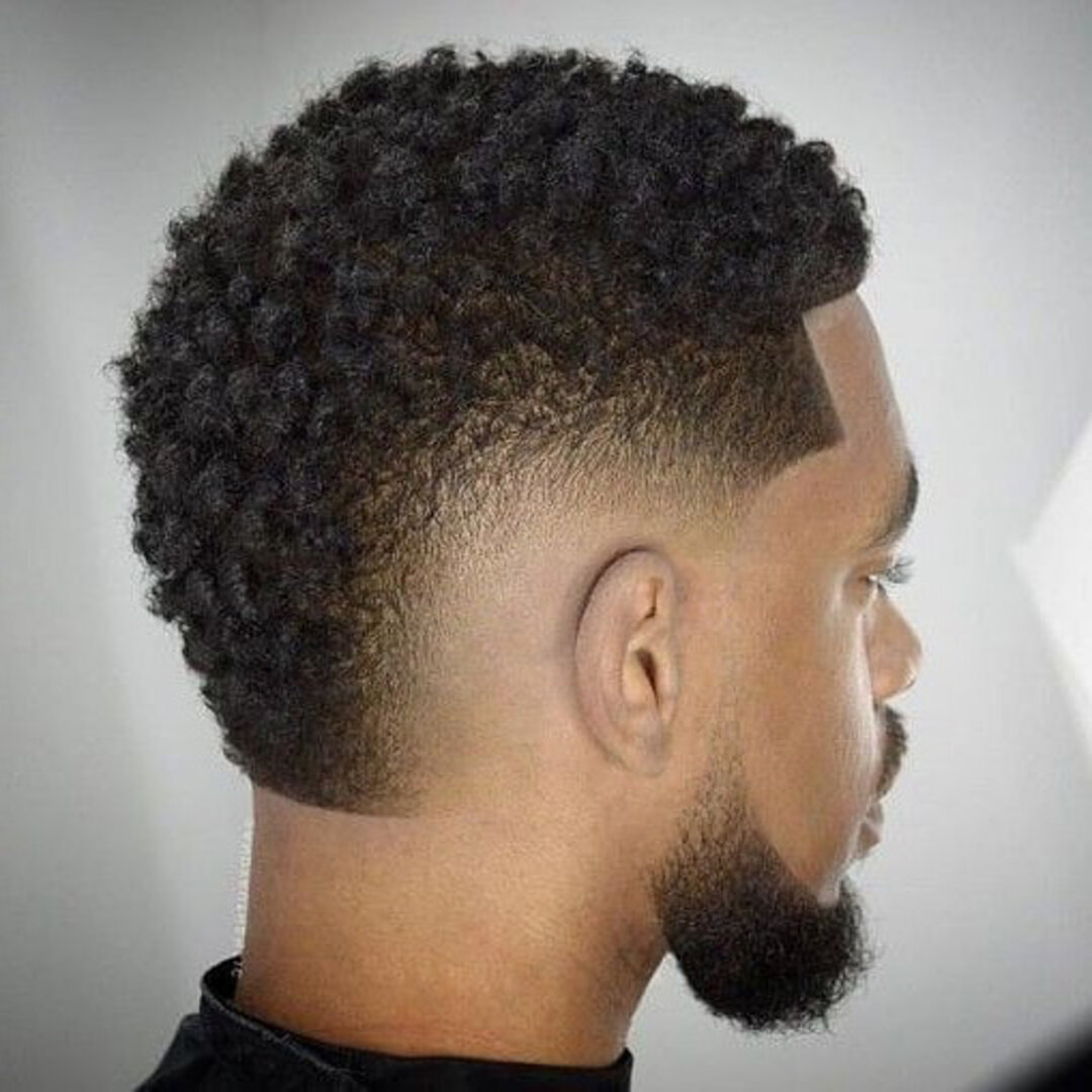 A black man with a temp fade hairstyle with twists and a black short beard.
