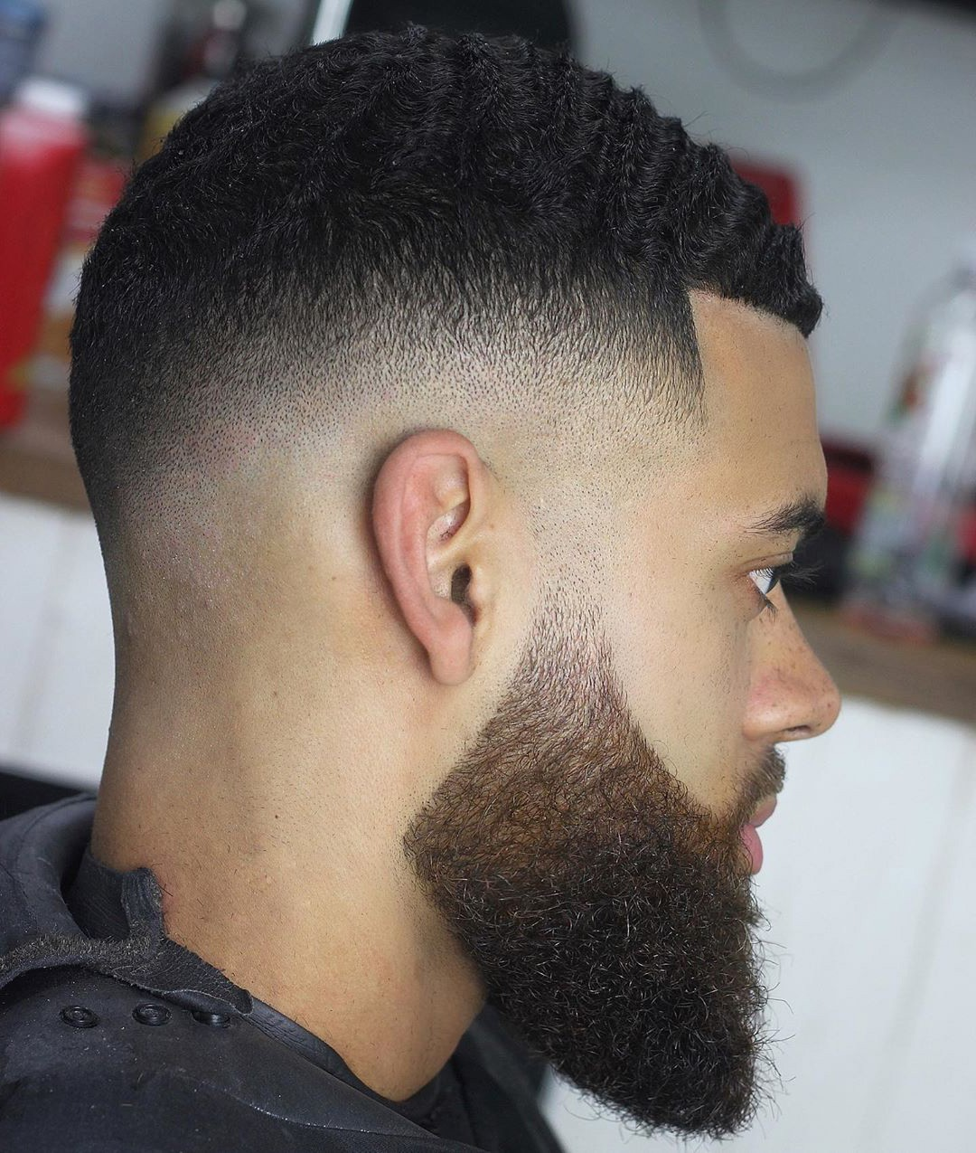 The man with a temp fade hairstyle with a beard a wavy hair.