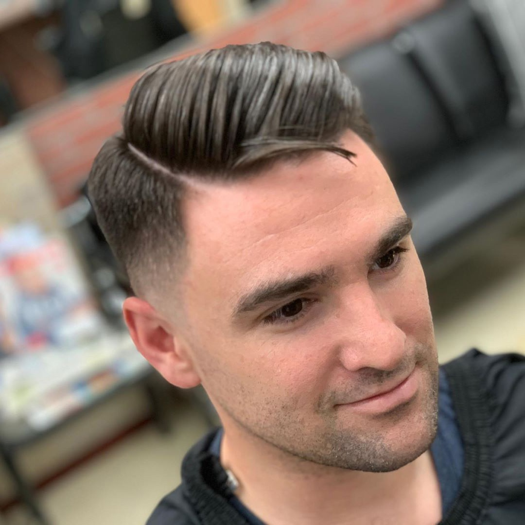A handsome man with a temple fade and comb over.