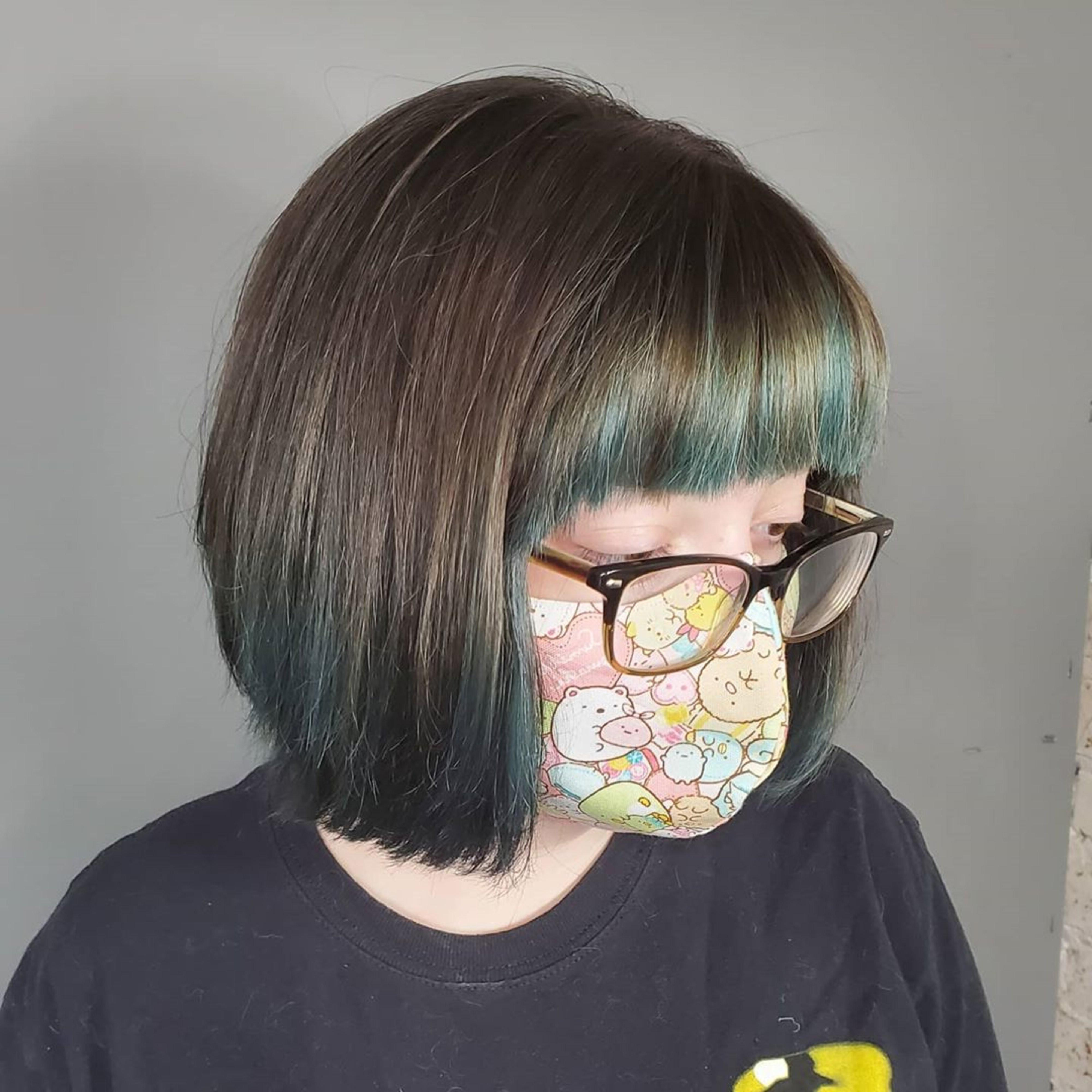 A mid-length bob haircut with bangs.