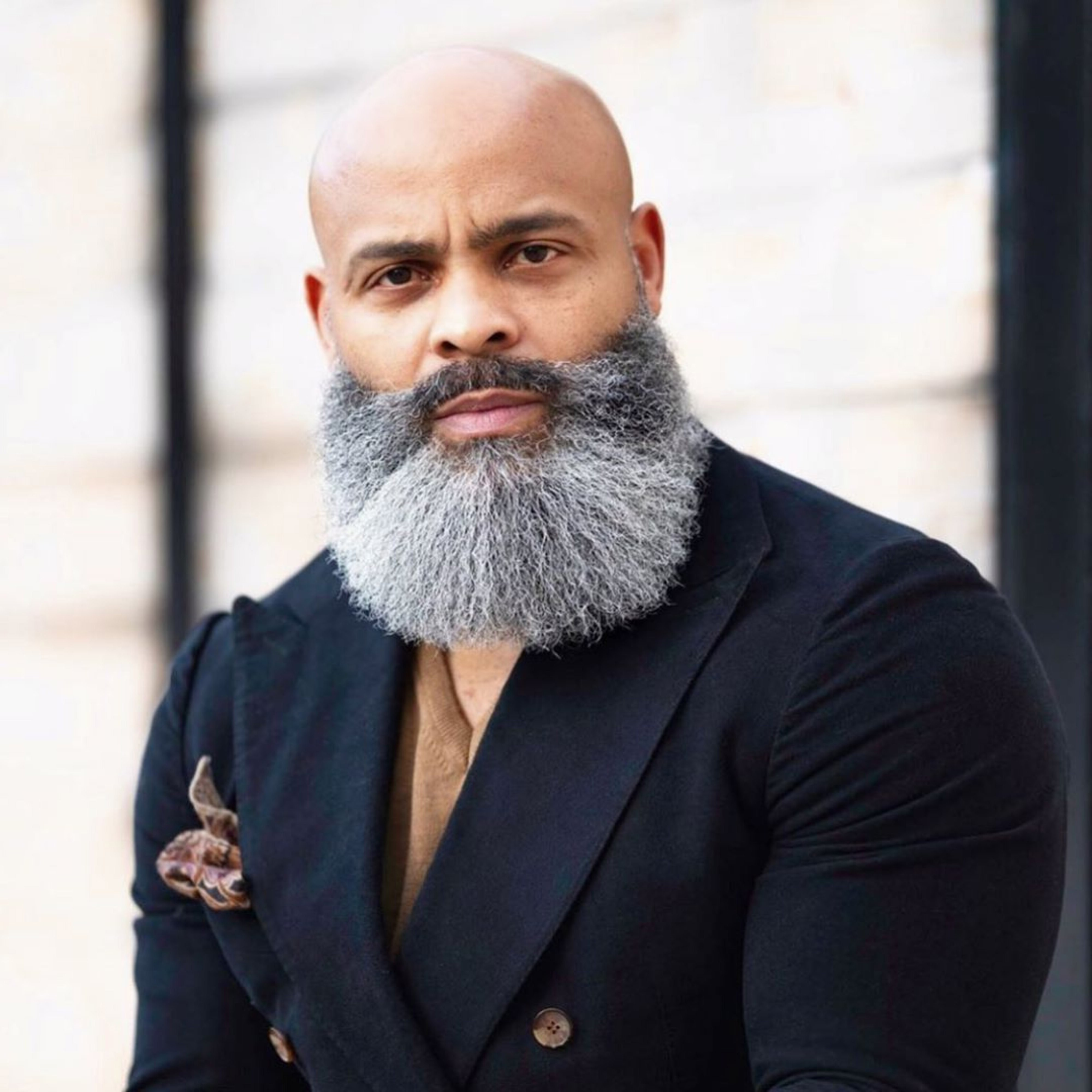 A shaved head style with a long beard.