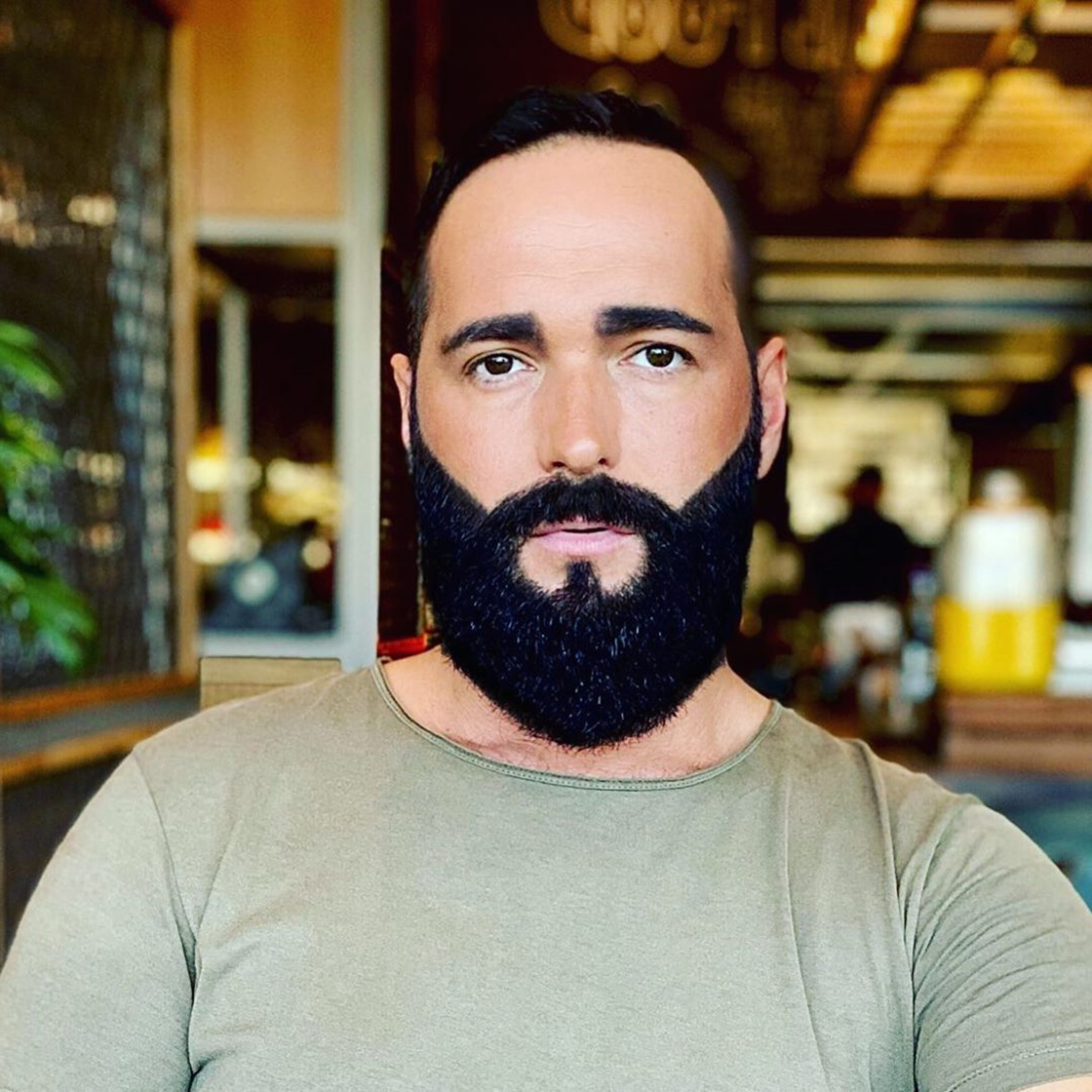 A low haircut with a full beard style.
