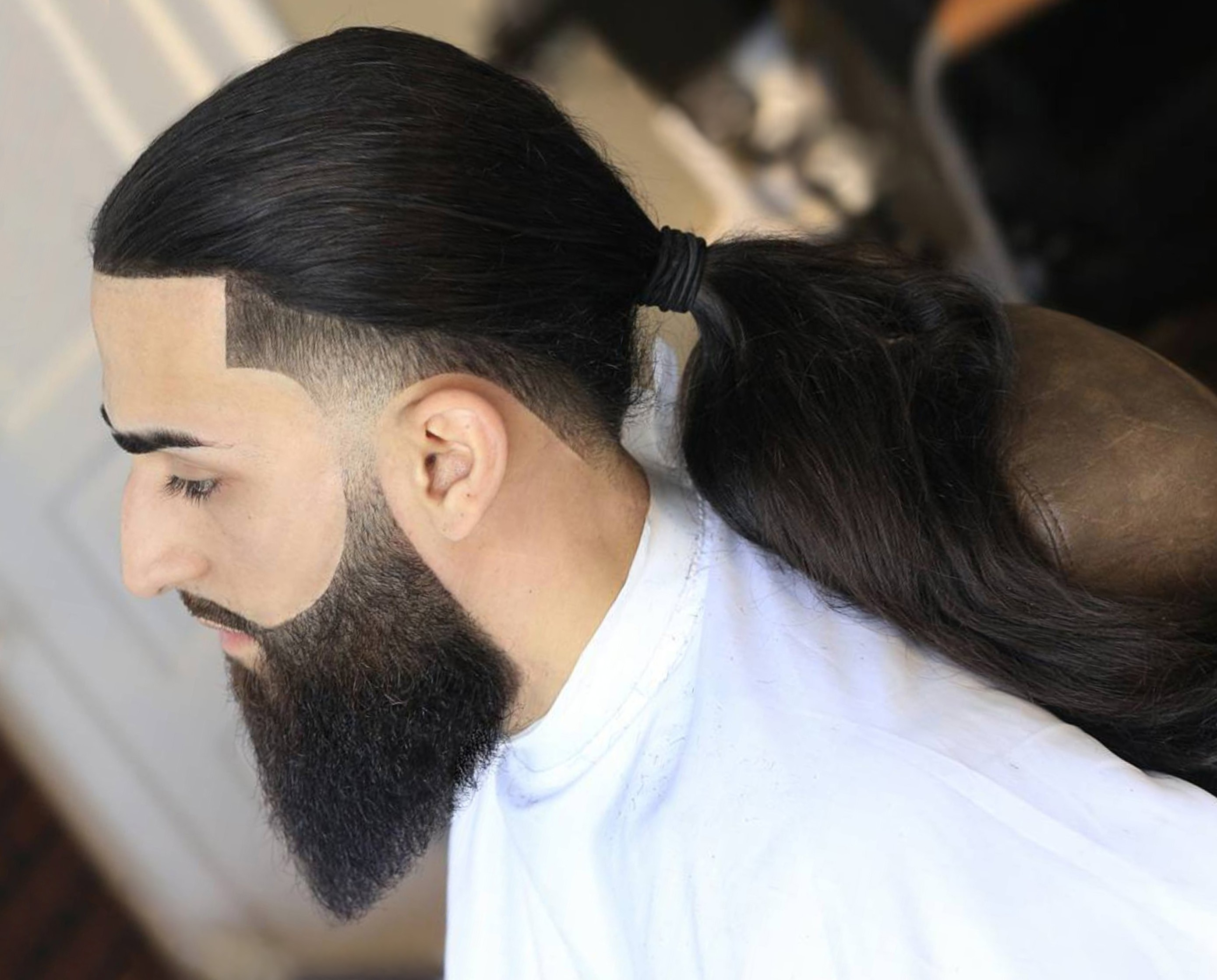 A full beard combined with a tapered fade cut.