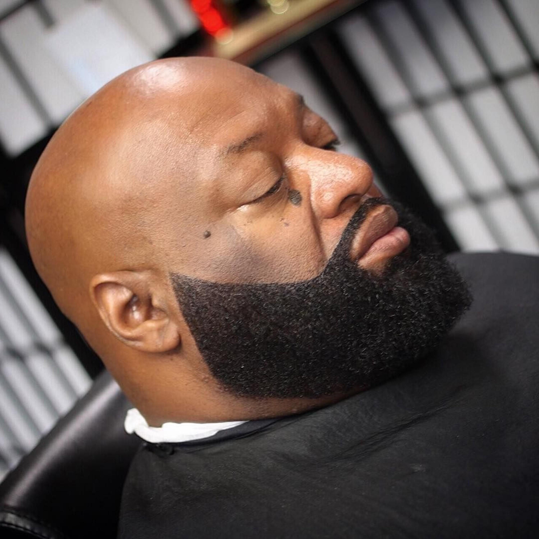 A bald black man with a stylish beard.