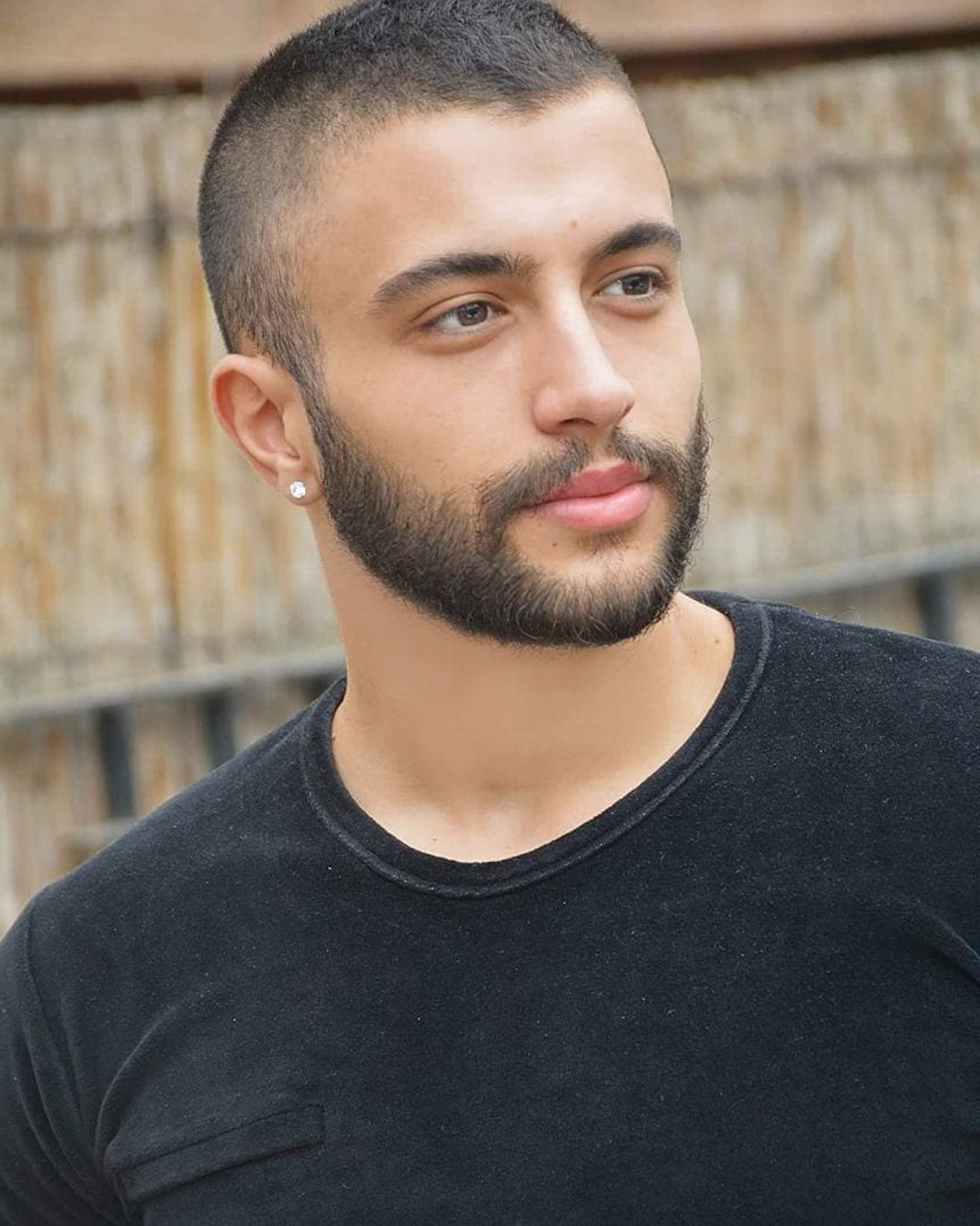A buzz cut with a stubble beard.