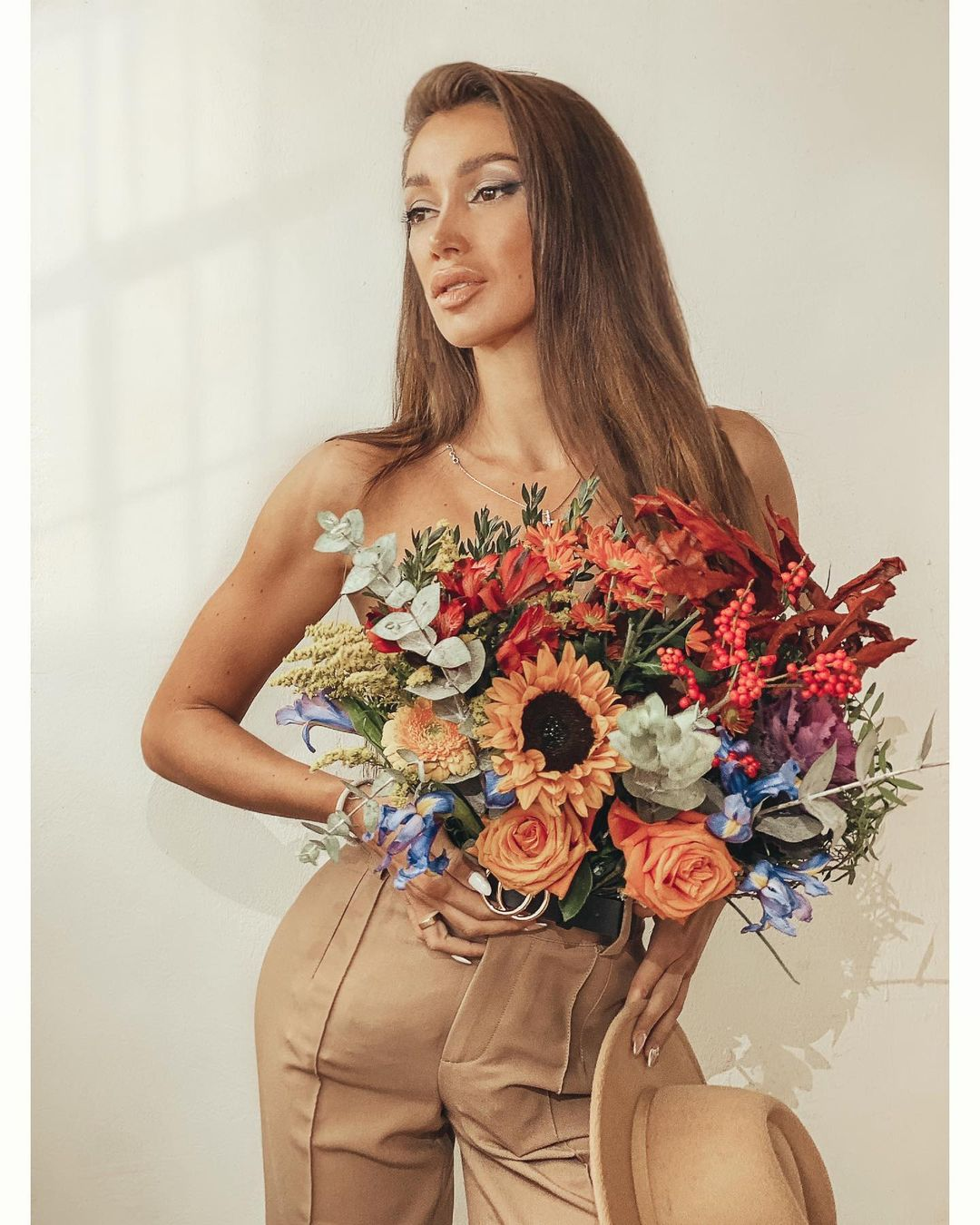 Elegant Julia Kashirova with a bouquet of flowers and long hair