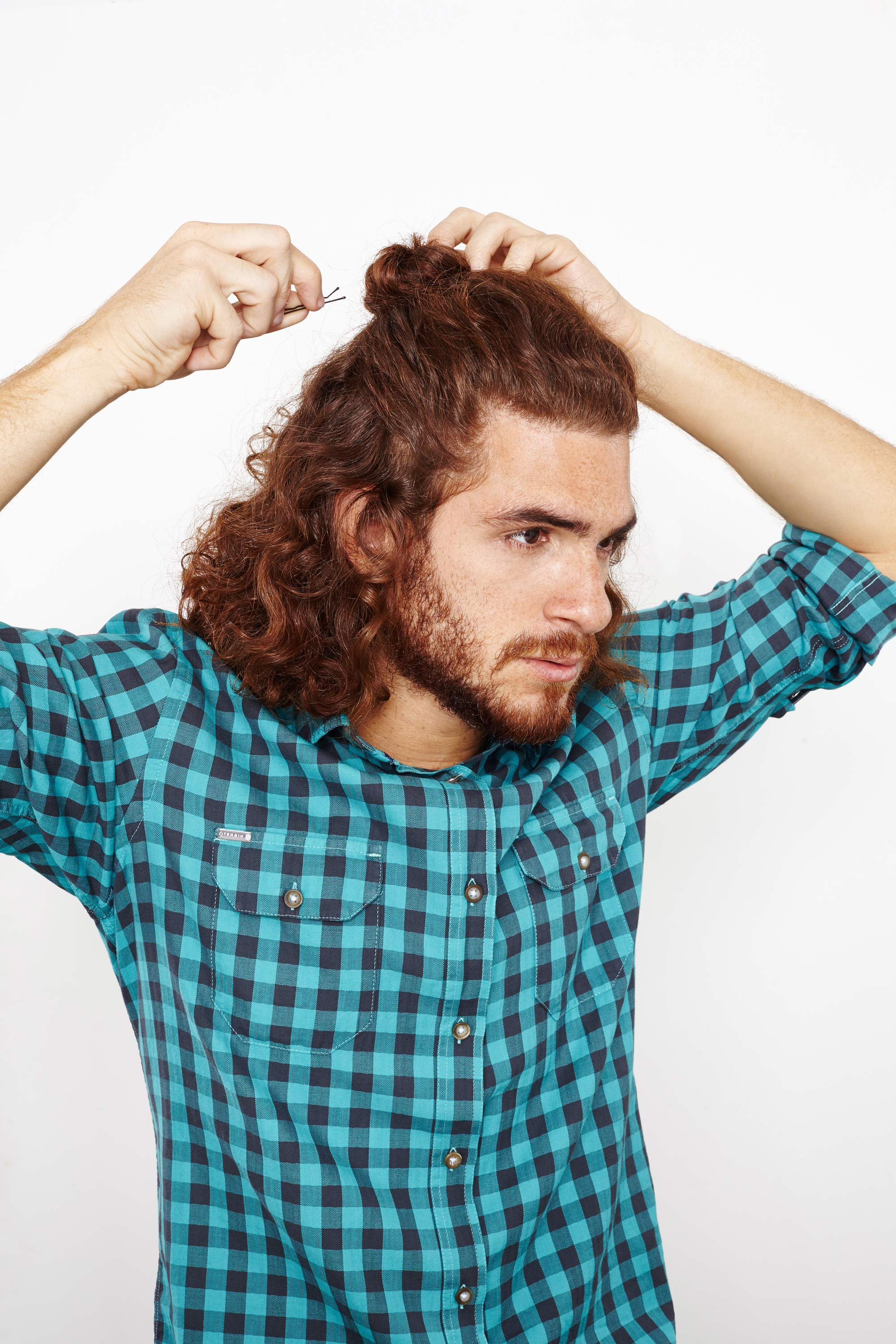 A half-up and down male hairstyle with a bun.