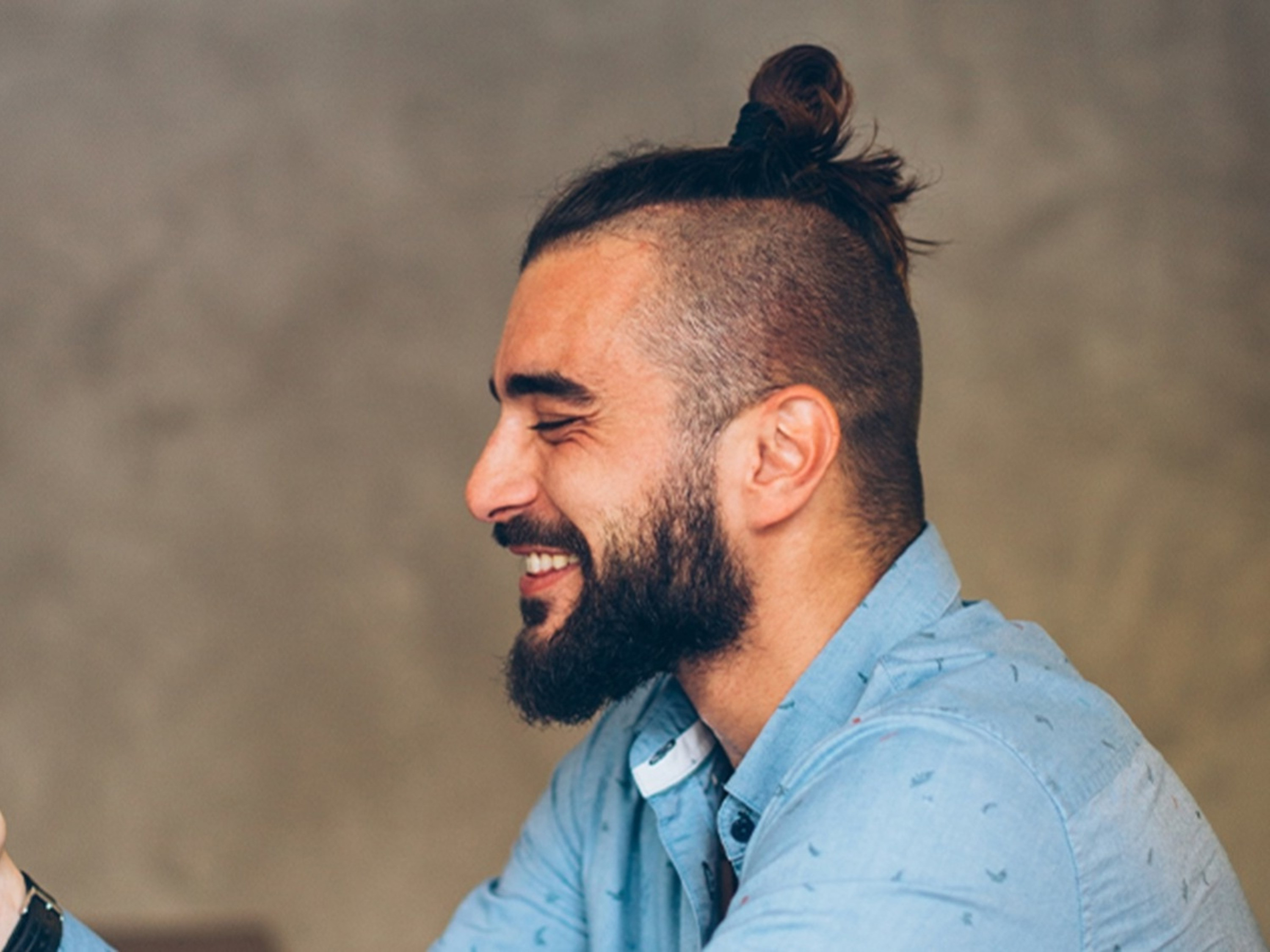 A high faded male hairstyle with a bun.