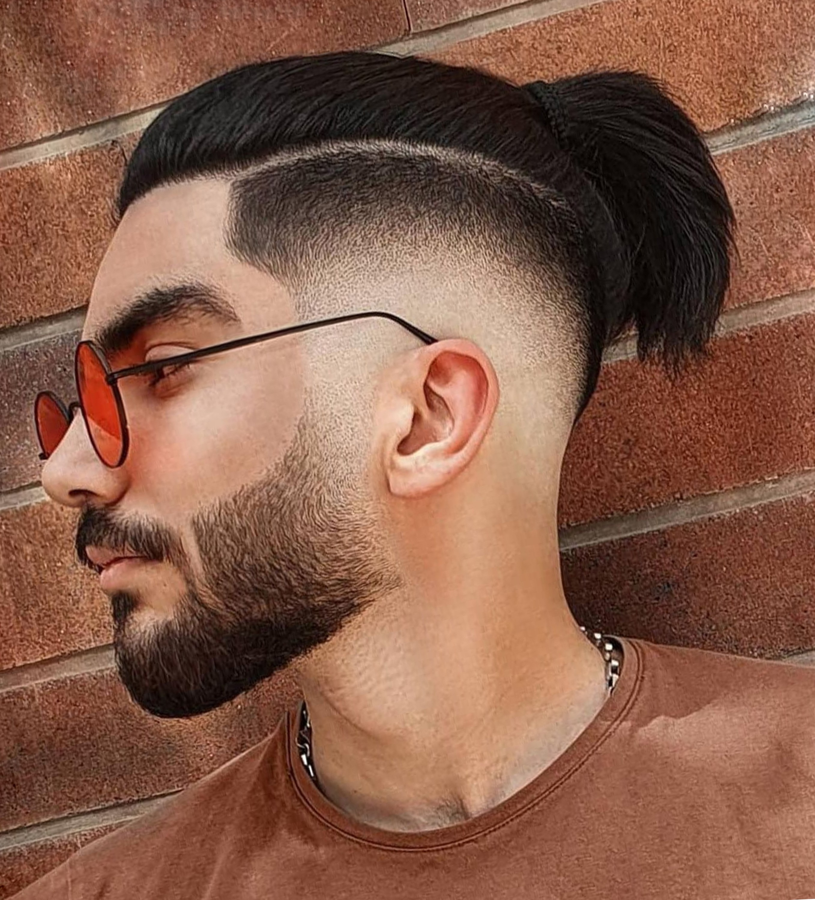 A low faded male haircut with a bun.