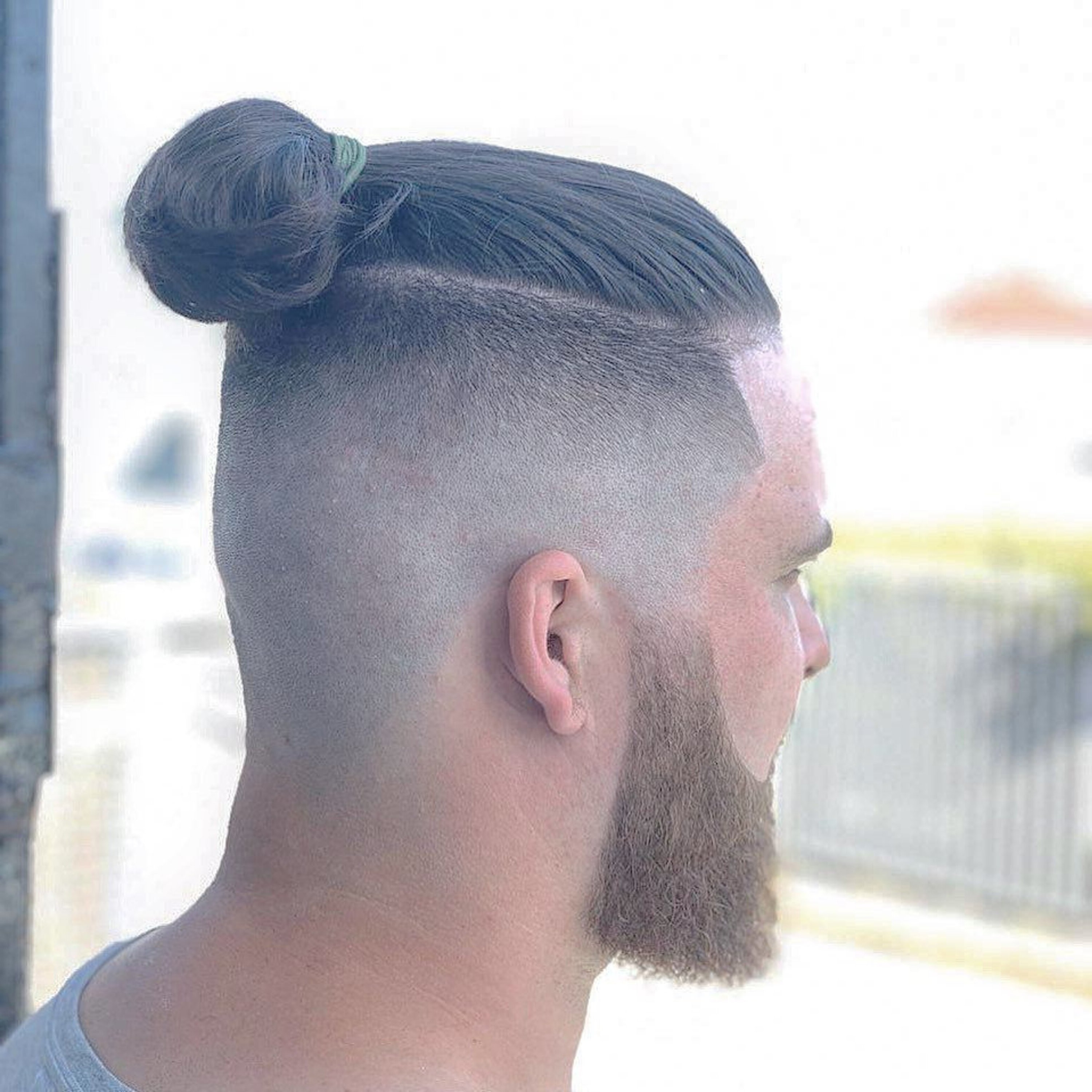 A male bun hairstyle with a comb over.