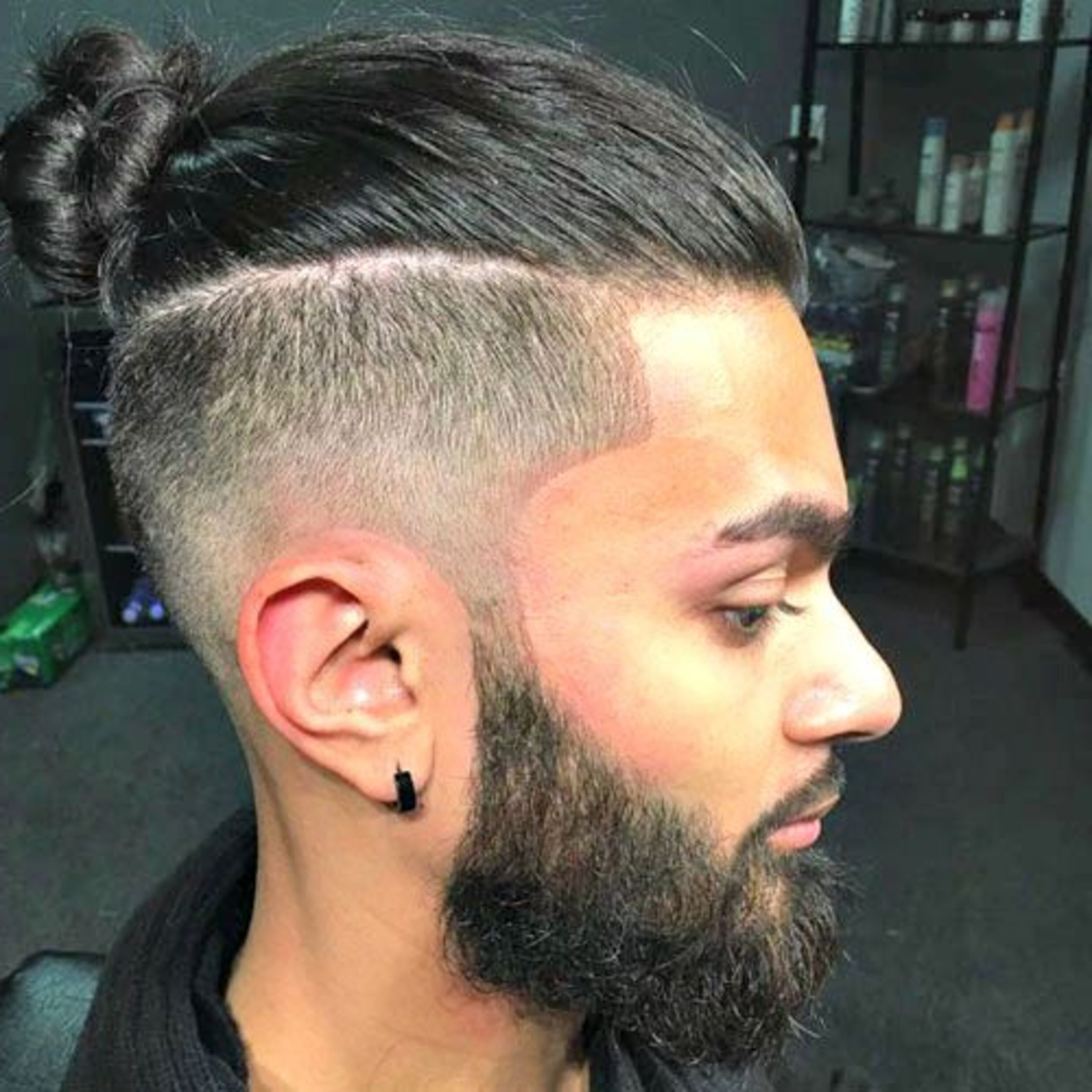 A male mid-faded haircut with a bun.