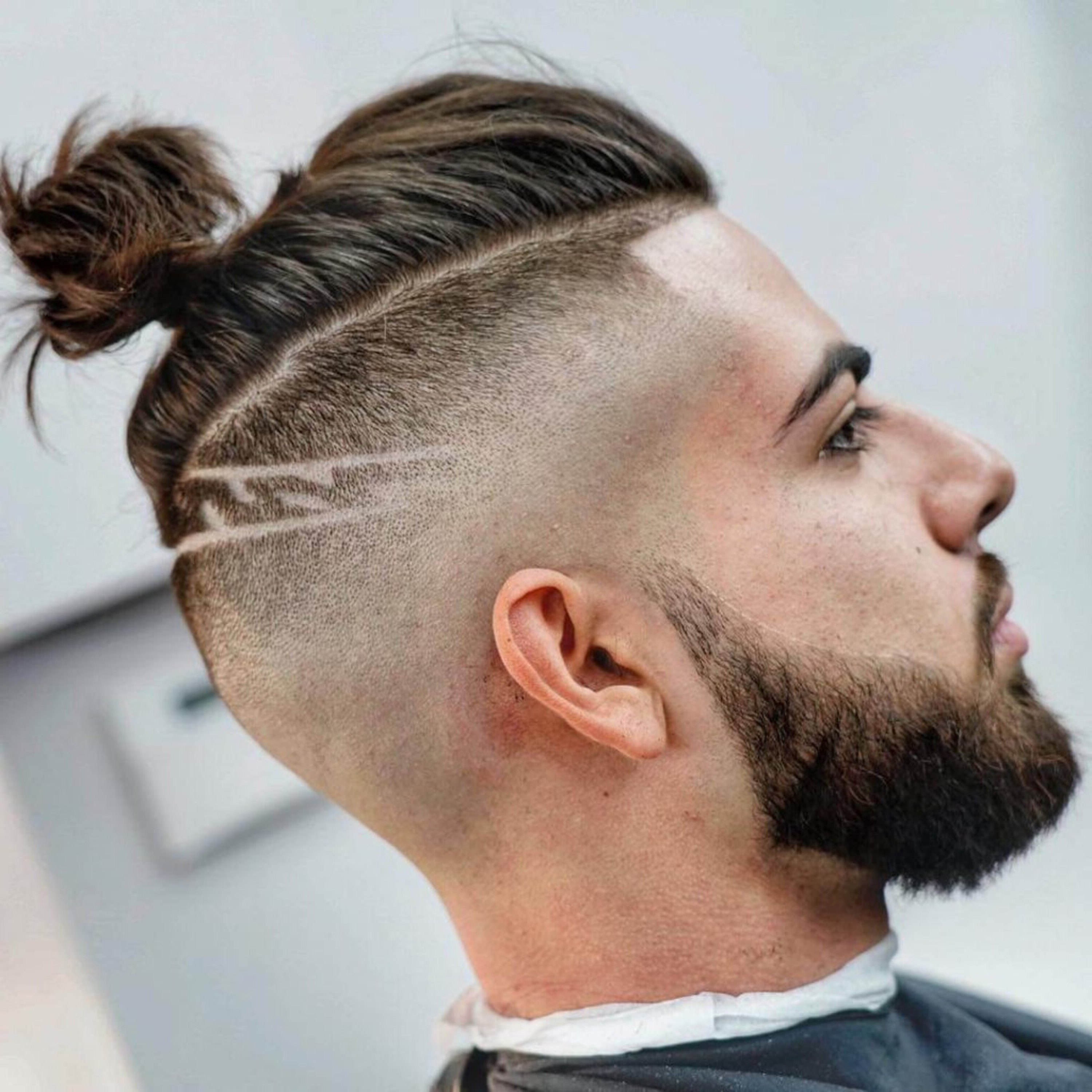 A male bun with the taper fade hairstyle.