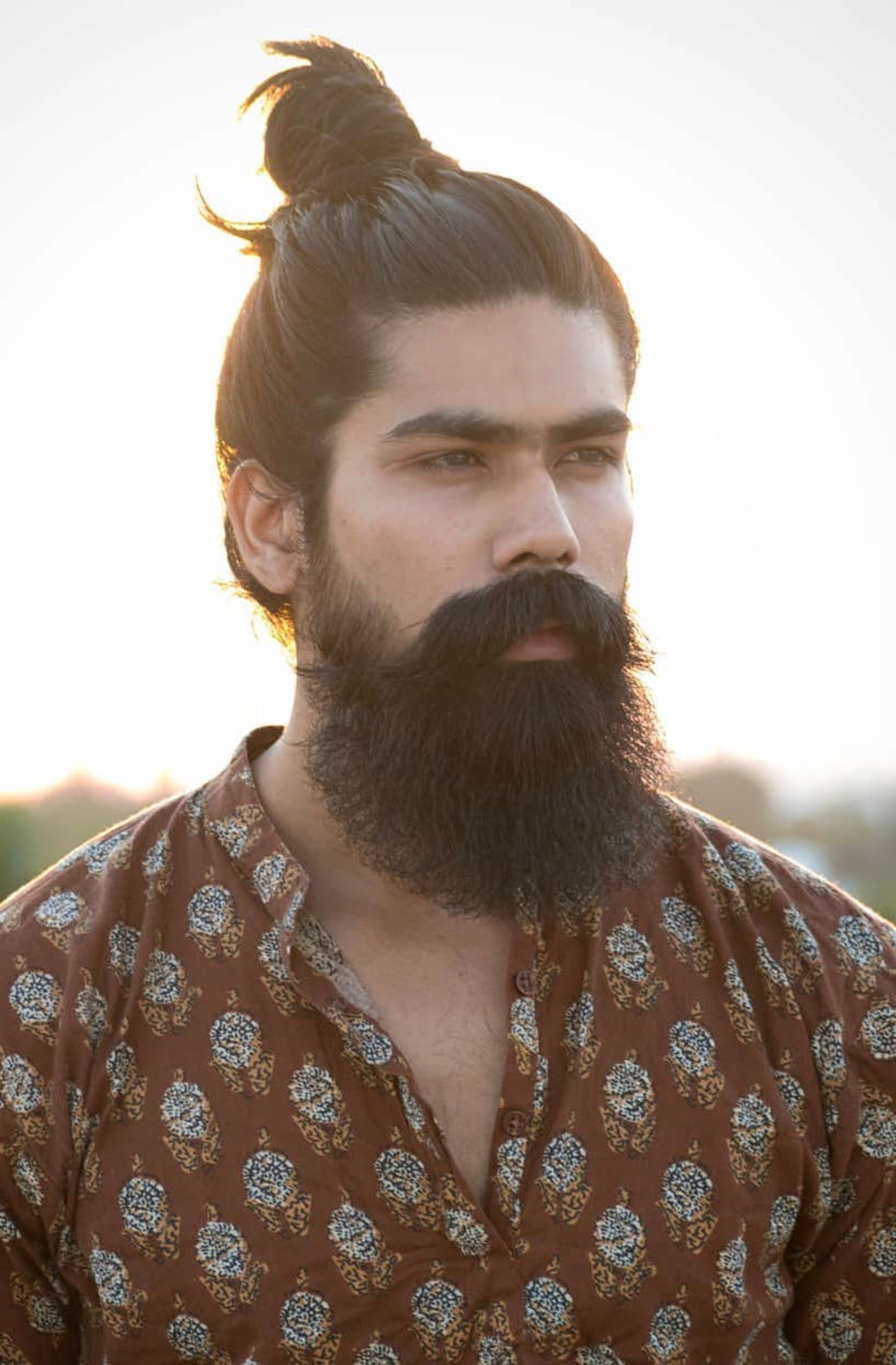 A bun hairstyle for men with thick hair.