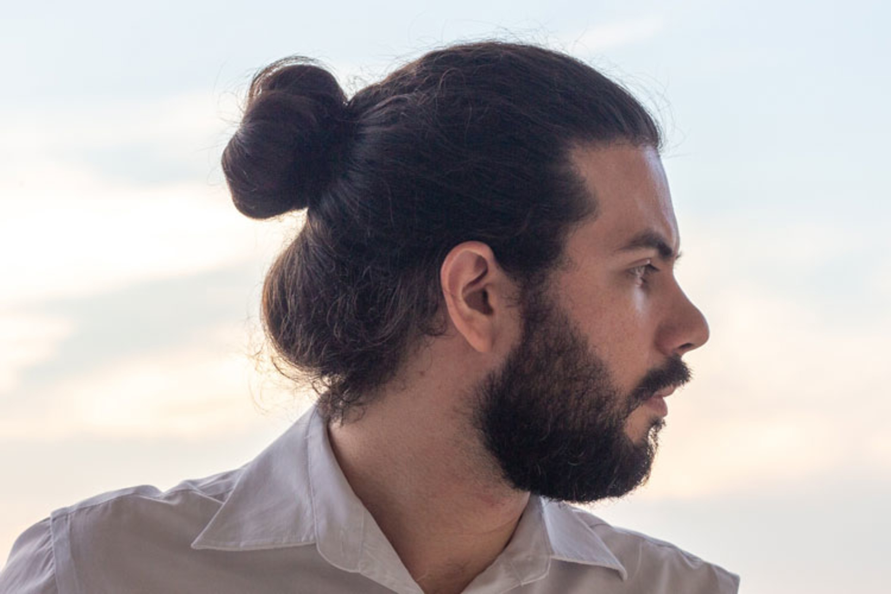 A bun haircut for men with the round face type.