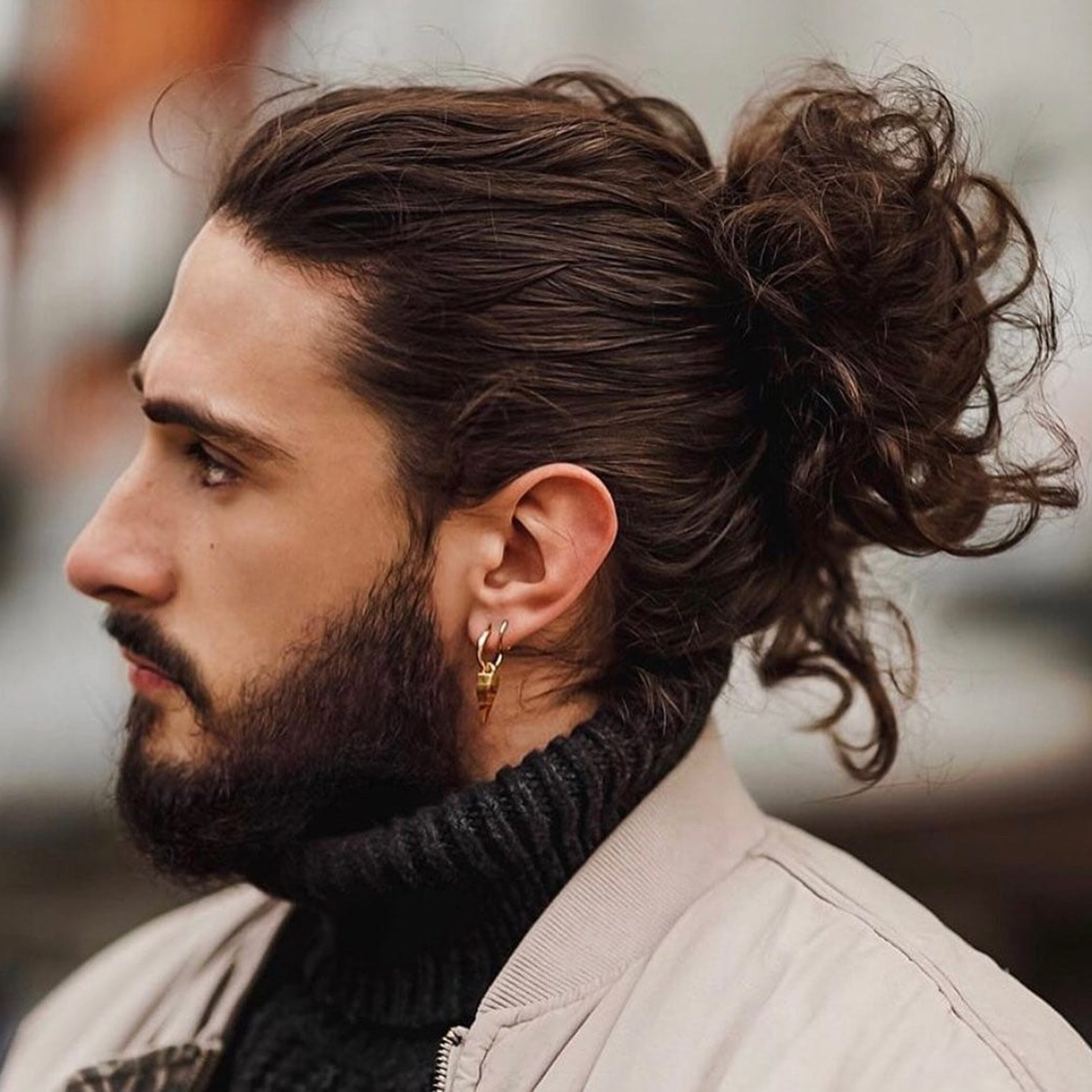 A wavy male hairstyle with a bun.