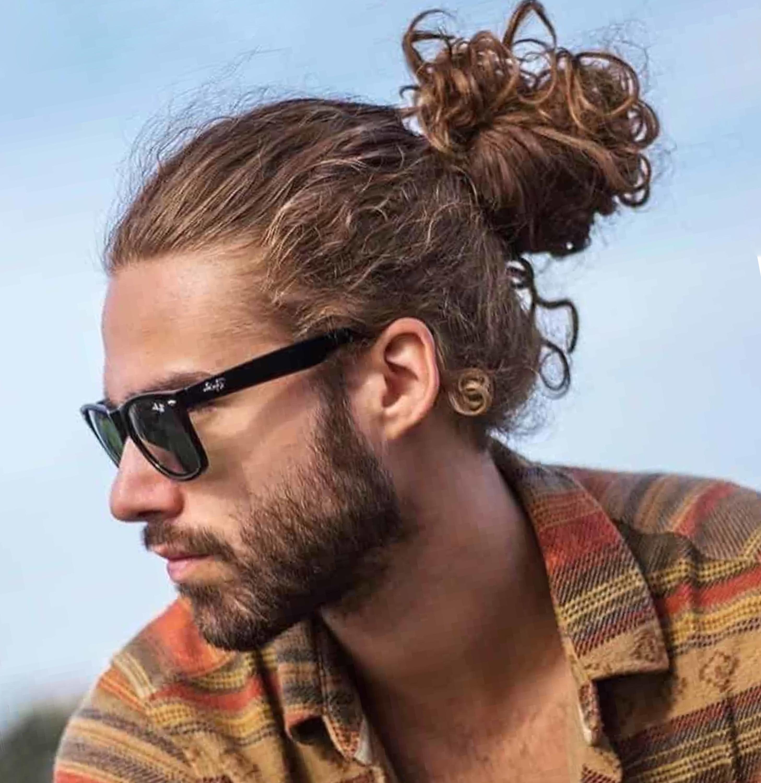 A scruffy male bun haircut.