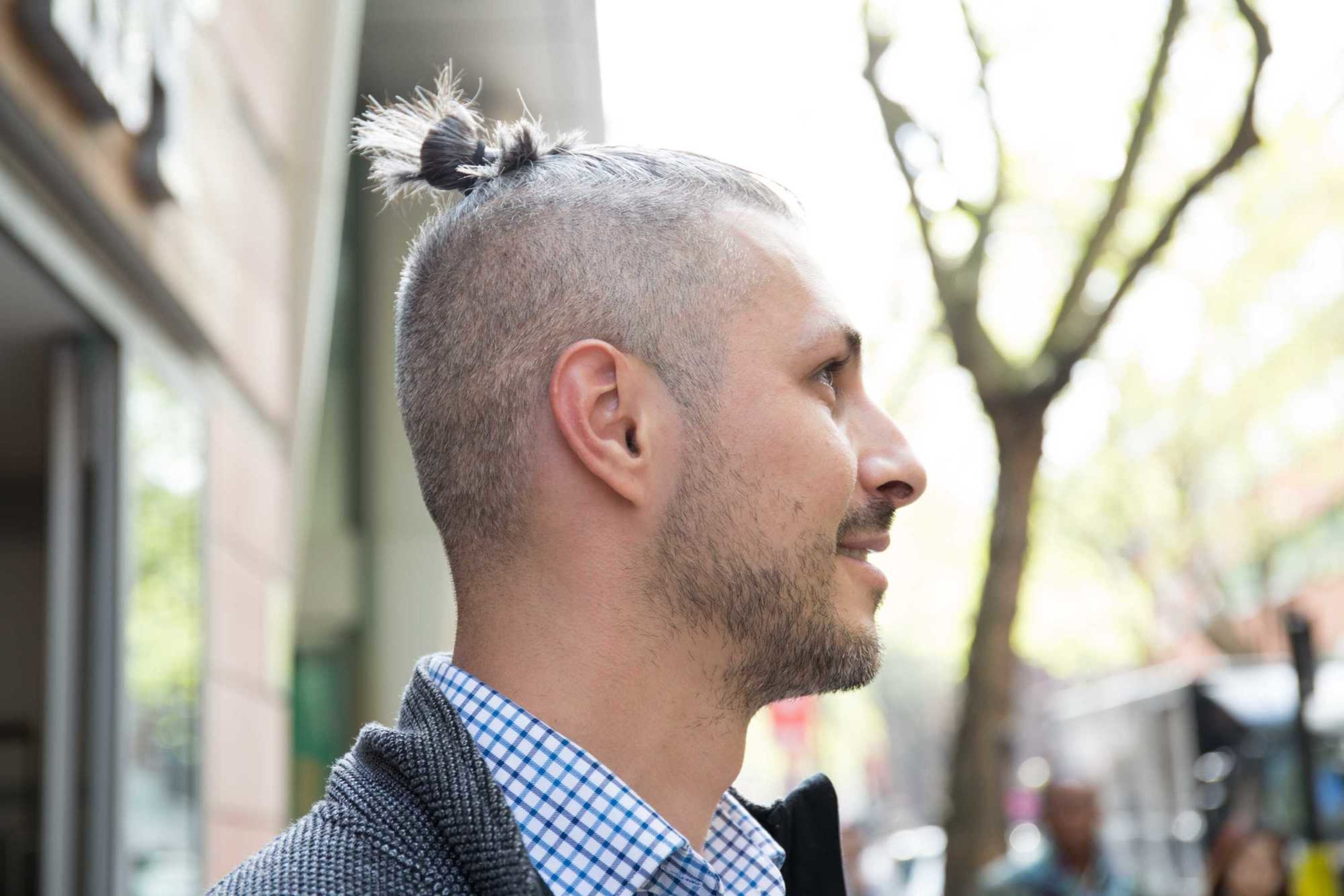 A shaved head hairstyle with a bun.